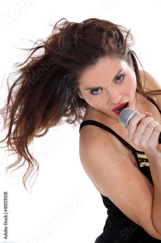 Photo  Attractive brunette singing into microphone