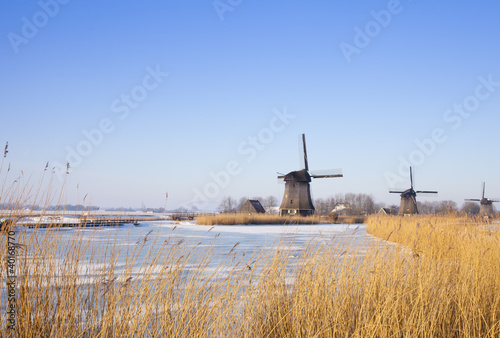 Aluminium Prints Mills Windmill in winter time with snow and blue sky