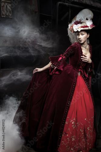 Obraz Beautiful woman wearing red dress over a train - fototapety do salonu