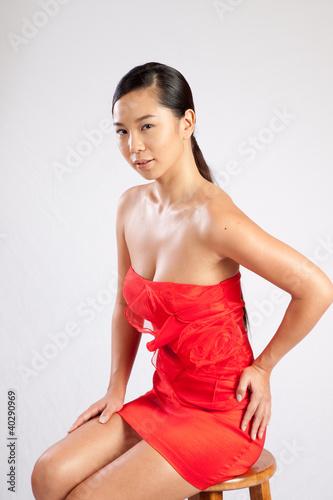 Foto  Südostasiatische Frau im roten Kleid, schaut nachdenklich