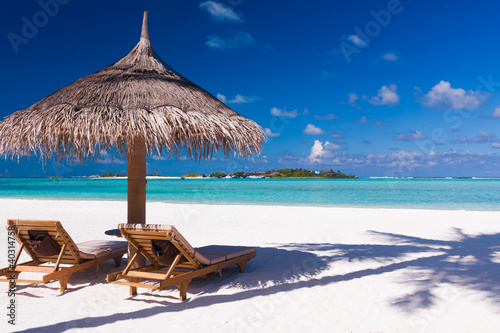 Foto-Schiebegardine Komplettsystem - Chairs and umbrella on a beach with shadow from palm tree (von Martin Valigursky)