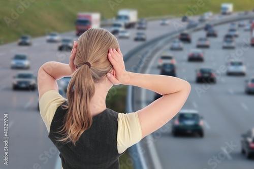 Fotografía  Frau mit Haenden an Ohren vor Autobahn