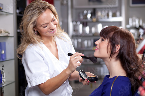 Spoed Foto op Canvas Bar Make up artist applying face powder toa customer in a beauty sto