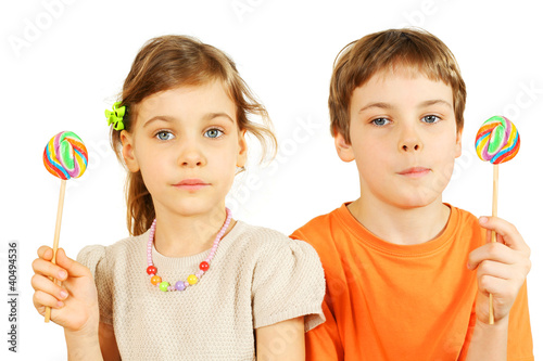 Fotografia, Obraz  Brother and sister hold colorful lollipops isolated on white