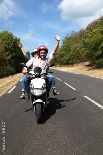 Couple enjoying scooter ride on country road Wallpaper Mural