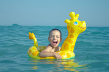 Happy Laughing Boy Swimming In Sea With Rubber Ring