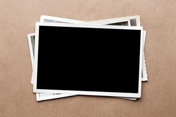 Fototapeta Stack of old photos on gray cardboard background