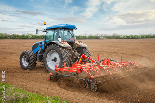 Fotografering  Small scale farming with tractor and plow in field