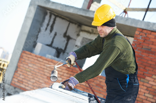 Flat roof covering works with roofing felt - Buy this stock photo