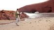 Man with laptop standing on the Legzira beach
