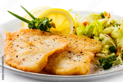 Fish dish - fried fish fillets and vegetable salad Fototapet