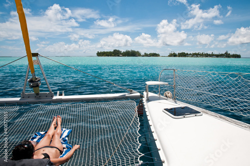 Young woman sunbathing on the catamaran Fotobehang