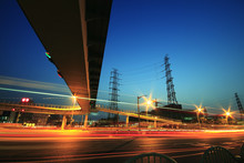 Long Exposure Of Cars Passing Through Of Transmission Tower