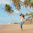 Fashion woman on tropical beach with photo camera