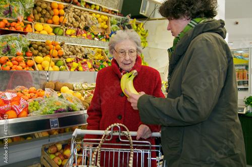 Leinwand Poster  Ältere Dame mit Betreuerin beim Einkaufen