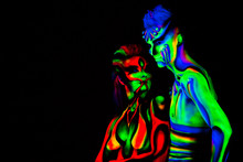 Man And Woman With Fluorescent Bodyart. Black Background. Studio
