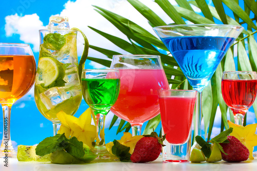 Glasses of cocktails on table on blue sky background - 41091355