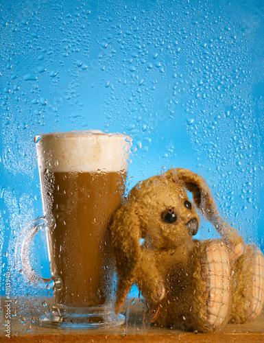 Fototapeta bunny and coffee latte behind rainy window, shallow dof on glass obraz na płótnie
