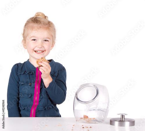 Girl stealing cookie out of cookie jar Fototapeta