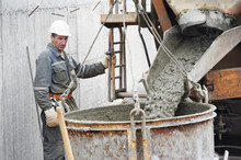 Builder Worker Pouring Concrete Into Barrel