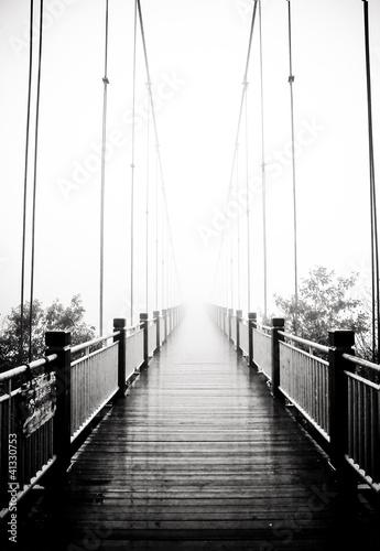 Fototapeta view on pedestrian wooden bridge in mist obraz
