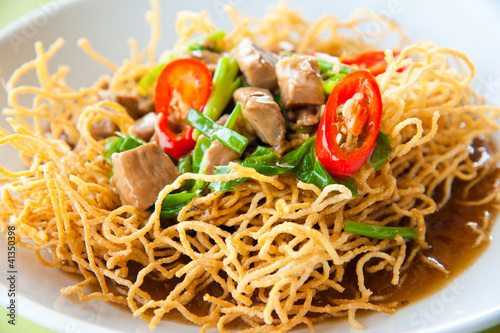 Photo  Chinese style deep fried yellow noodles with pork and soup