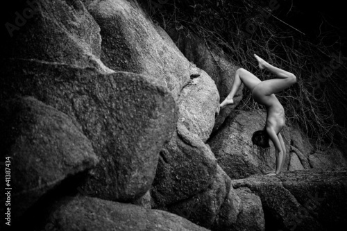 a beautiful young girl standing on his hands on the stones - 41387434