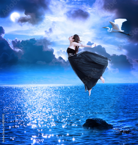 Fotobehang Volle maan Beautiful girl jumping into the blue night sky