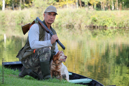 Photographie Un chasseur et son chien près d'une rivière.
