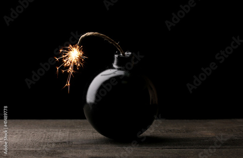 Cartoon style bomb on wooden table on black background Poster