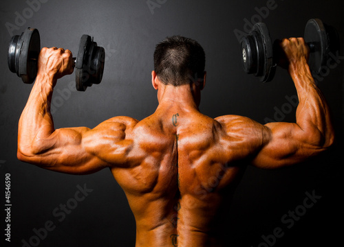 Fotografia  rear view of bodybuilder training with dumbbells