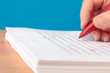canvas print picture - Hand with Red Pen Proofreading a Manuscript Closeup