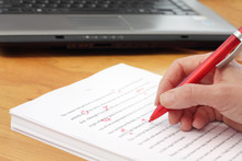 Hand With Red Pen Proofreading...