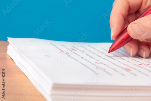 Photo Hand with Red Pen Proofreading a Manuscript Closeup
