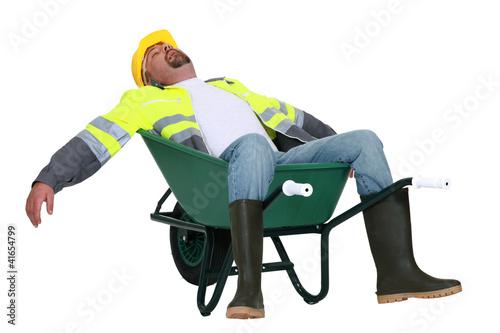 Obraz Tradesman asleep in a wheelbarrow - fototapety do salonu