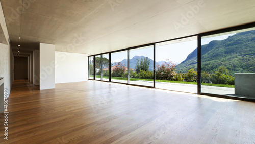 Obraz modern concrete house with hardwood floor, wide open space - fototapety do salonu