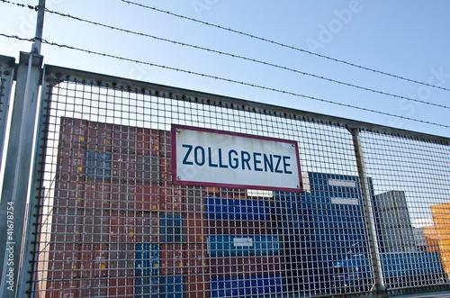 Fotografie, Obraz  Stacheldraht Zaun mit Schild Zollgrenze vor Container Lagerplatz