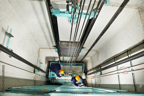 Photo  machinists adjusting lift in elevator hoistway