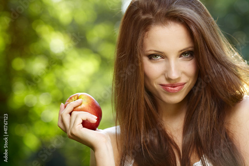 Woman with apple in garden Canvas-taulu