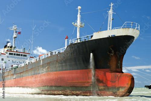 Foto auf AluDibond Schiff Cargo ship run aground on rocky shore