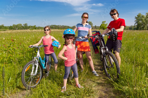 Photo Stands Cycling Happy family on bikes, cycling outdoors. Family sport