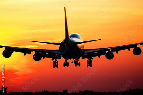 Fotografia  Plane landing by sunrise