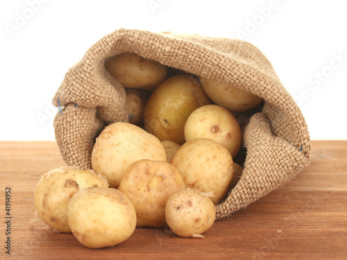 young potatoes in a sack on a table on white background