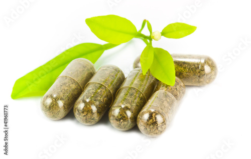 Fotografia  herbal medicine pills with green plant on white background