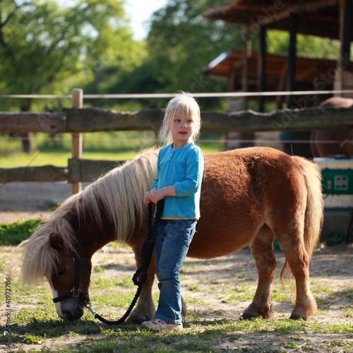 Fotografie, Obraz  kleines Mädchen führt Pony spazieren