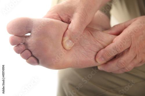 Fotografie, Obraz  a man checks his aching foot