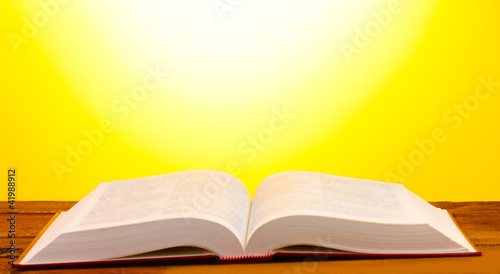 Open book on wooden table on yellow background Canvas Print
