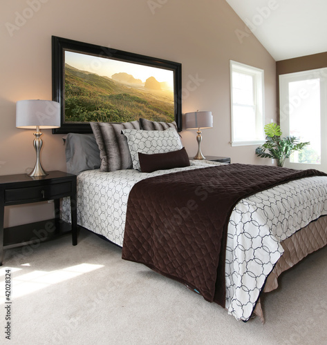 Photo  Modern brown and white bed with nightstands.