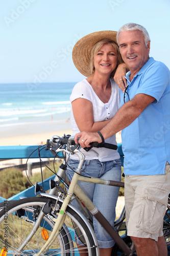 Plakaty o zdrowiu   starsza-para-z-rowerami-przy-plazy