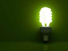 Energy Saving Light Bulb Glowing On Green